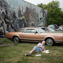 Bob O'Connor eats on the grass beside a row of vintage cars at Arcade Park on the opening day of the Pullman National Monument in the Pullman neighborhood, Saturday afternoon, Sept. 4, 2021.
