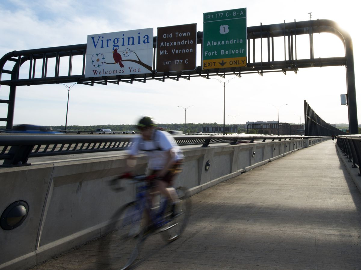 A person rides a bicycle down a bike path on Woodrow Wilson Memorial Bridge.