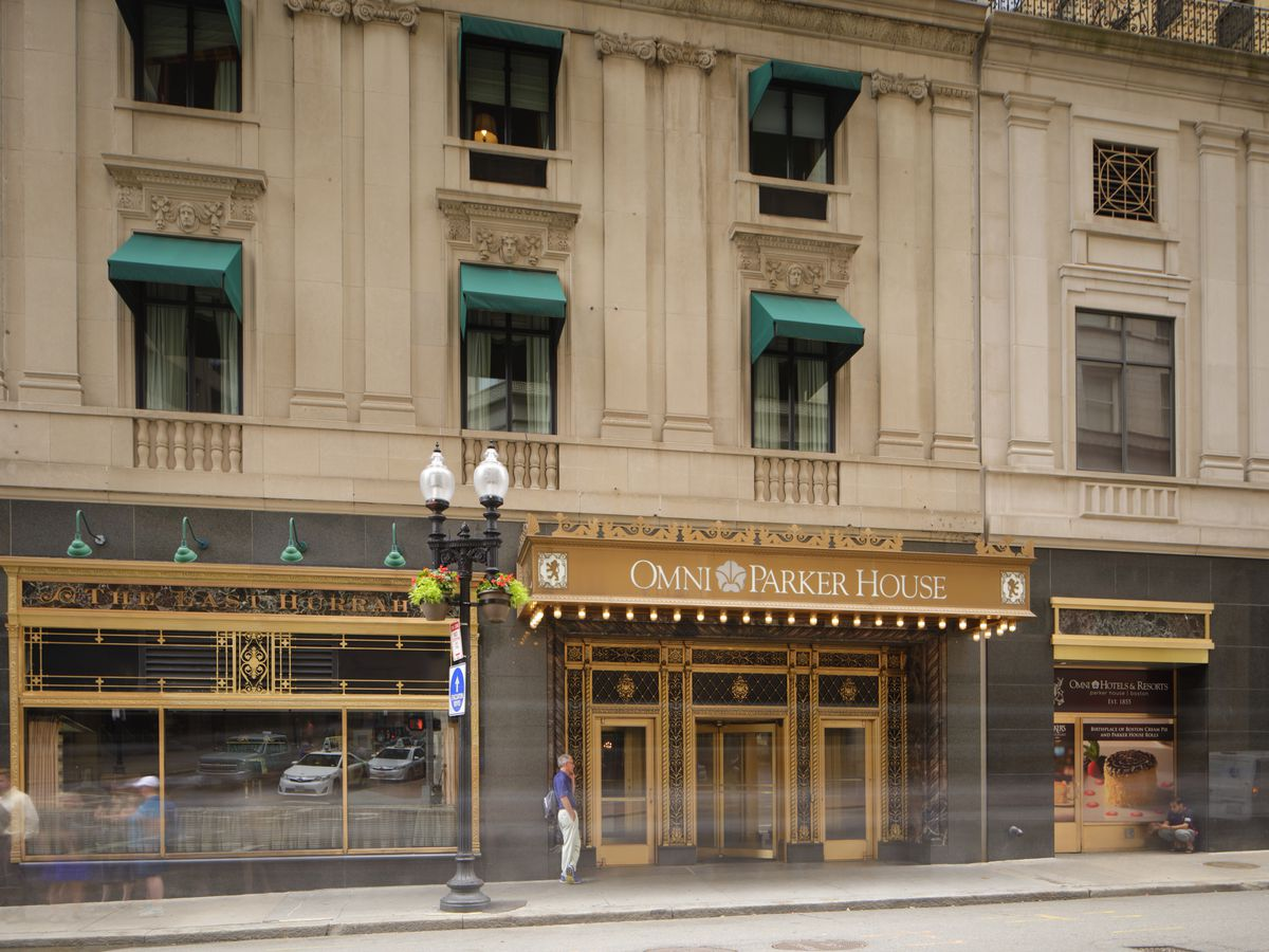 The exterior of a multi-story hotel fronting on a sidewalk, with a firm awning extending over its entrance.