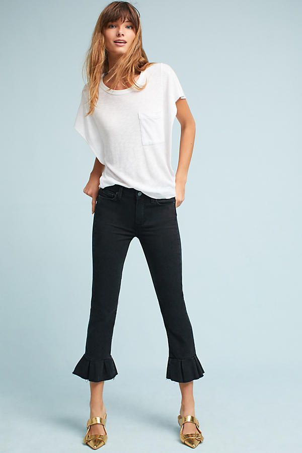 643f0a22f53d95 A model in black ruffle jeans and a white tee