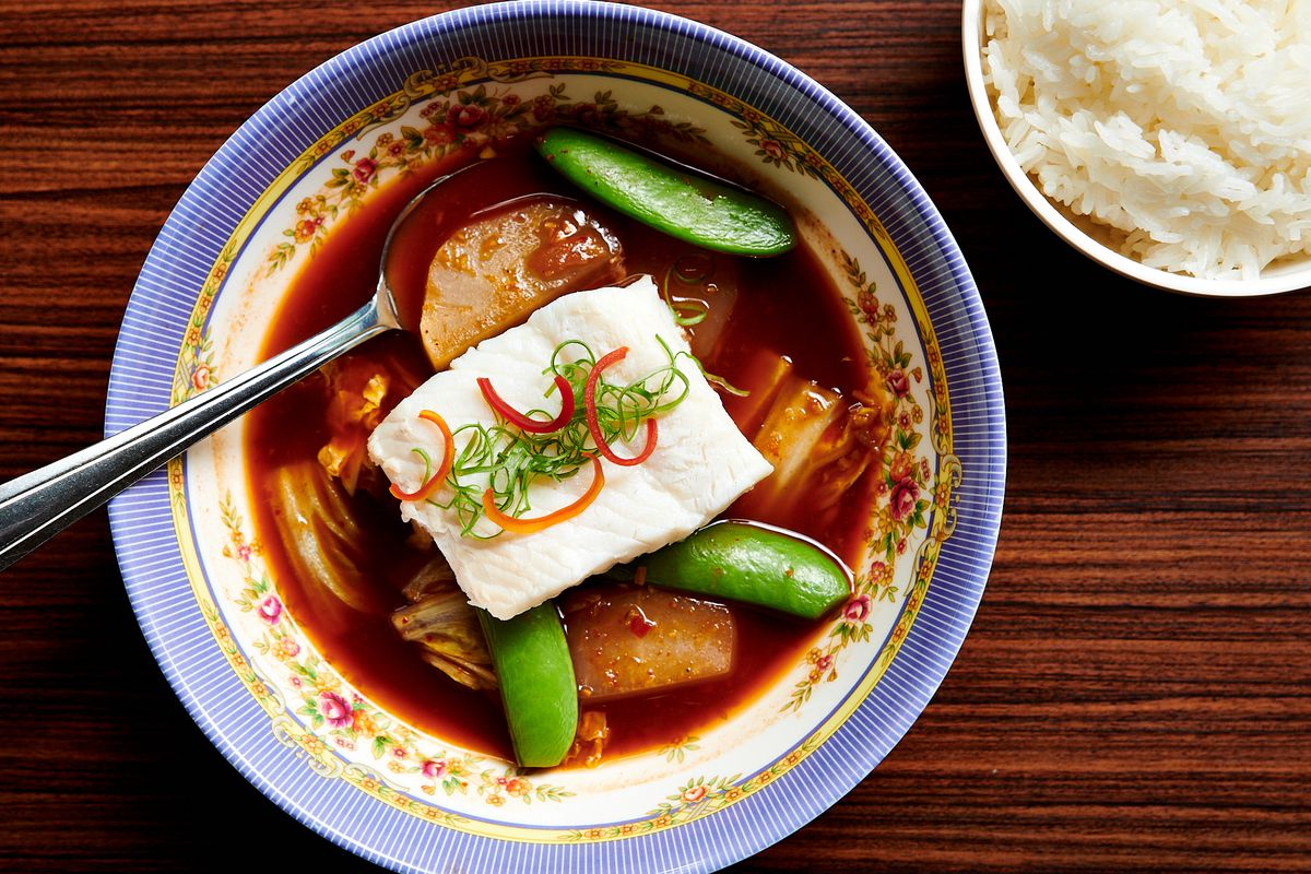 A picture of a red bowl of coconut-milk-free curry with a single chunk of halibut, pieces of cabbage, and snap peas. The curry is served in an ornate bowl with a side of rice.