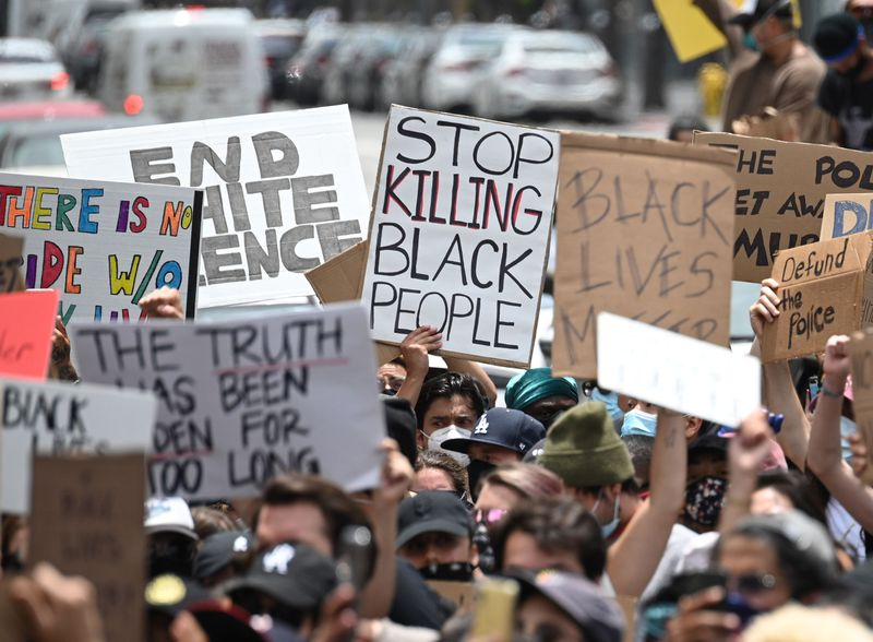 """Protesters on a street hold up signs that read, """"Stop killing black people,"""" """"Defund the police,"""" """"Back lives matter,"""" and, """"End white violence."""""""