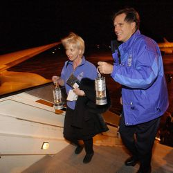 SLOC members Mitt Romney and Cindy Gillespie carry the  Olympic Torch flame lantern and one of four backup lanterns onto the Delta Airlines 777 in Athens, Greece, Dec. 4, 2001.