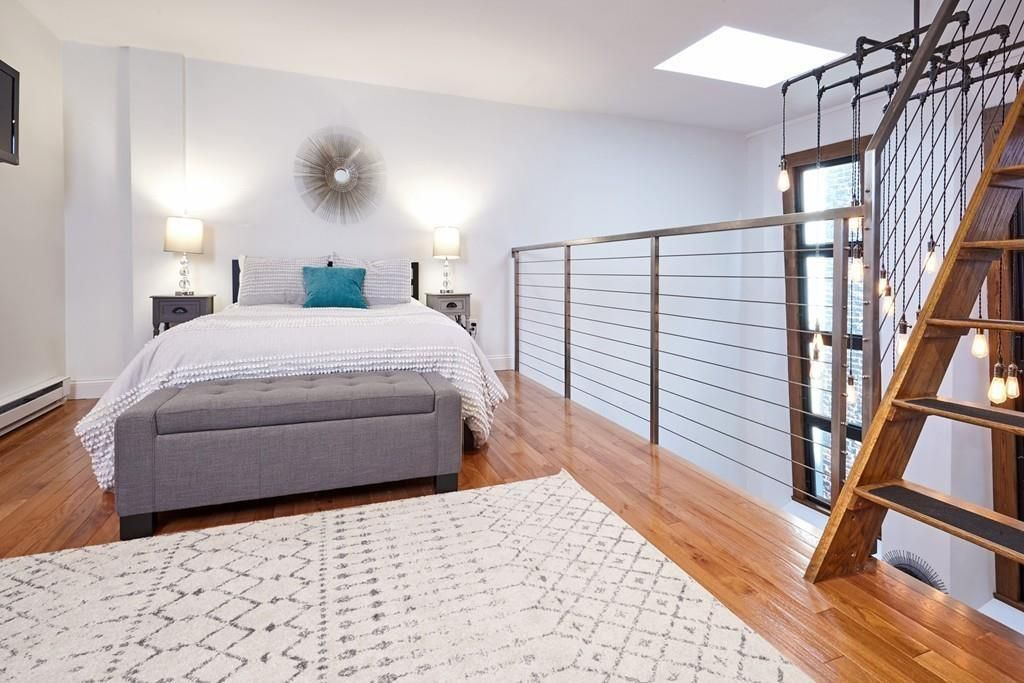 An open bedroom next to a railing and with a staircase leading up, and there's a bed.