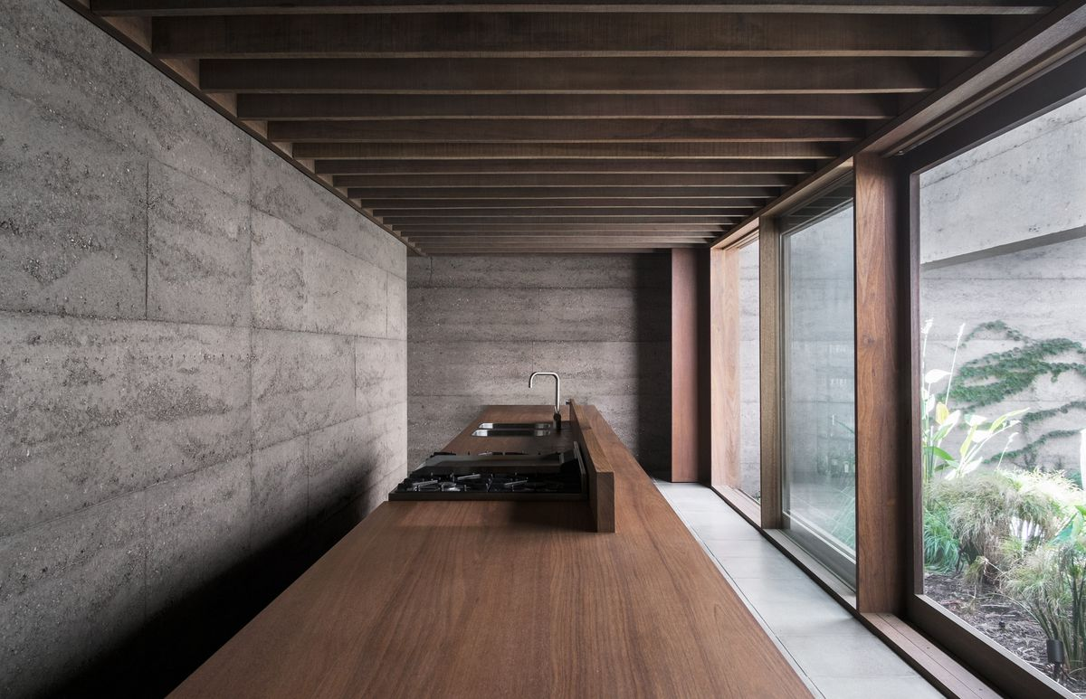 Kitchen with concrete walls and timber ceiling