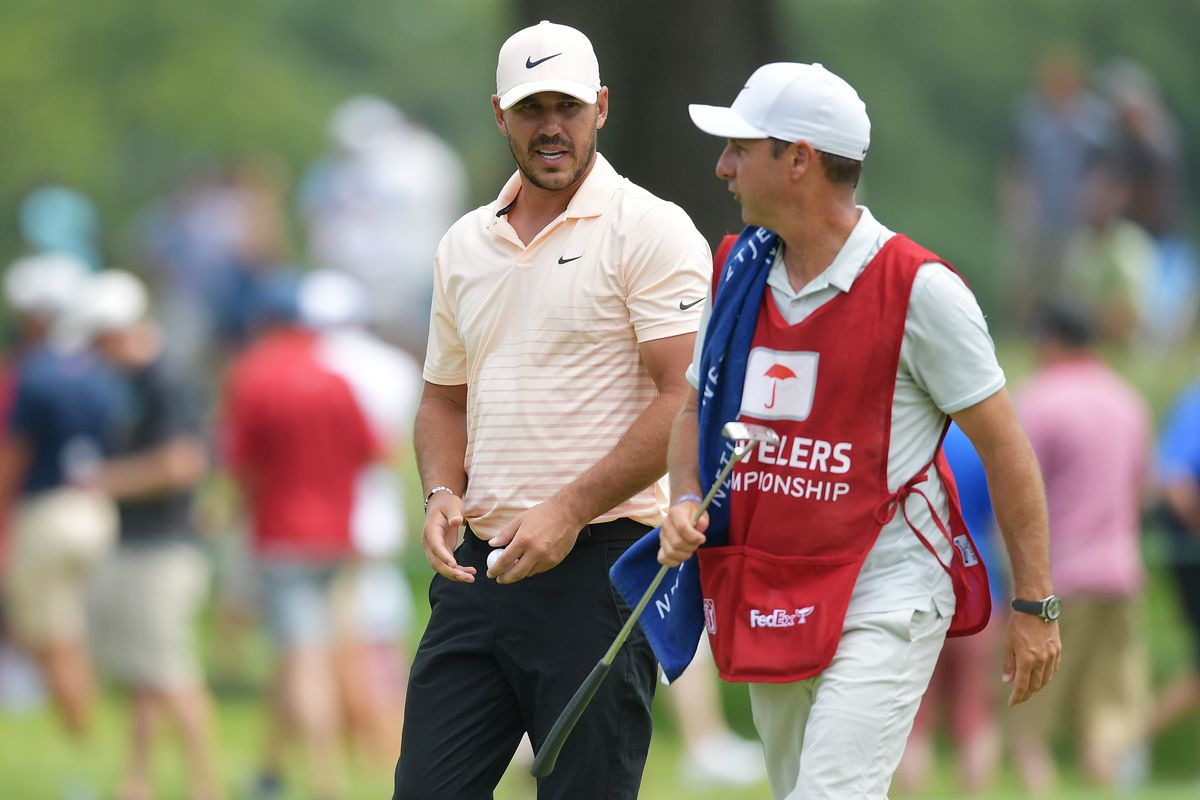 Brooks Koepka of the United States talks with his caddie Ricky Elliott on the fourth green during the final round of the Travelers Championship at TPC River Highlands on June 27, 2021 in Cromwell, Connecticut.