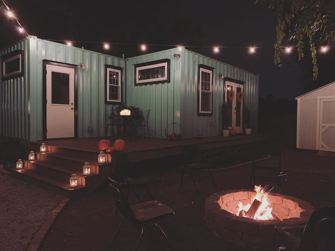 The blue container home at night.