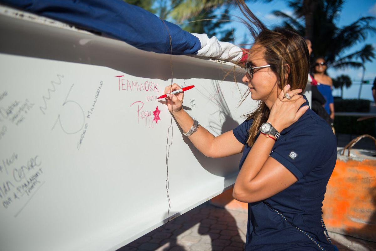 A woman in a blue shirt signs a white beam that will rise to the top of a new luxury condo tower