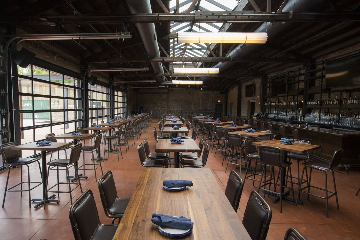 A warehouse-style bar and restaurant space with long wooden tables.