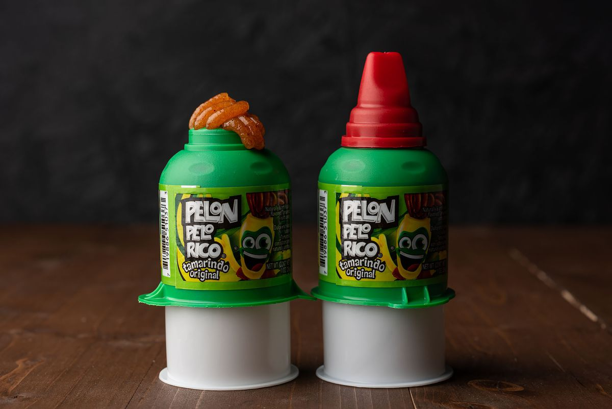 Two Pelon Pelo Ricos, one without the cap and tamarind paste squeezing through the top