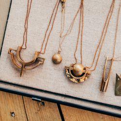 "<b>Metalepsis</b> The W Neclace, <a href=""http://www.internationalplayground.com/women/accessories/jewelry/metalepsis-the-w-necklace.html""> $110</a>. <b>Metalepsis</b> The Q Necklace, <a href=""http://www.internationalplayground.com/women/accessories/jewel"