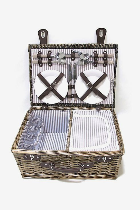 A wicker picnic basket with four place settings