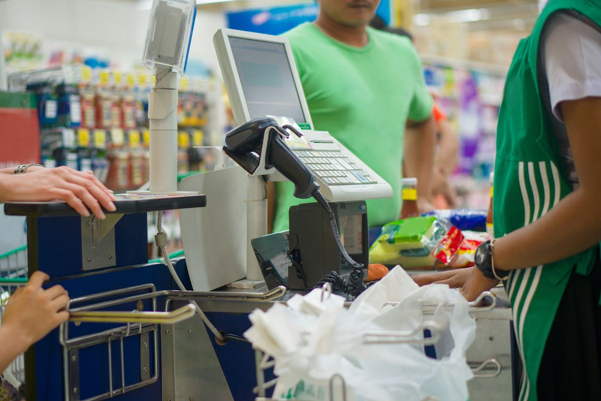 A grocery worker in a green smock stands at a register checking out customers