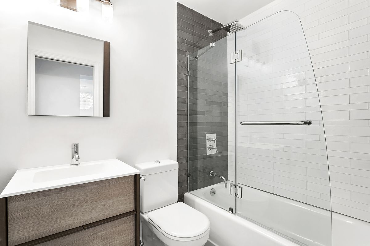 A bathroom with white walls and tiles.