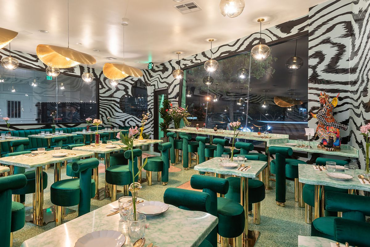 A fancy dining room at night with green velvet chairs and dizzying wallpaper.