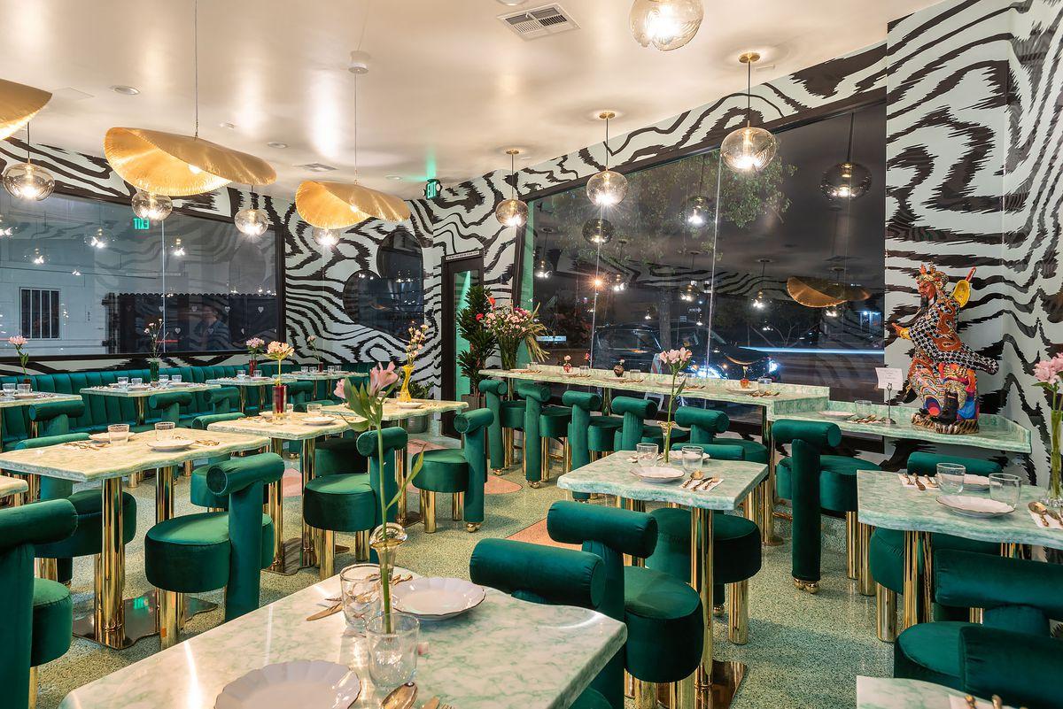 Elegancka jadalnia w nocy z zielonymi aksamitnymi krzesłami i oszałamiającą tapetą.