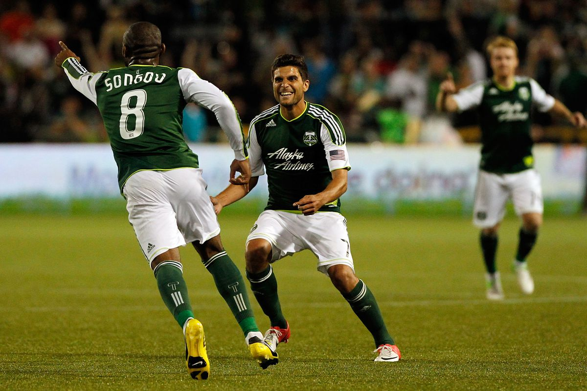 PORTLAND, OR - AUGUST 25: Frank Songo'o #8 of the Portland Timbers celebrates a goal with Sal Zizzo #7 against the Vancouver Whitecaps on August 25, 2012 at Jeld-Wen Field in Portland, Oregon. (Photo by Jonathan Ferrey/Getty Images)