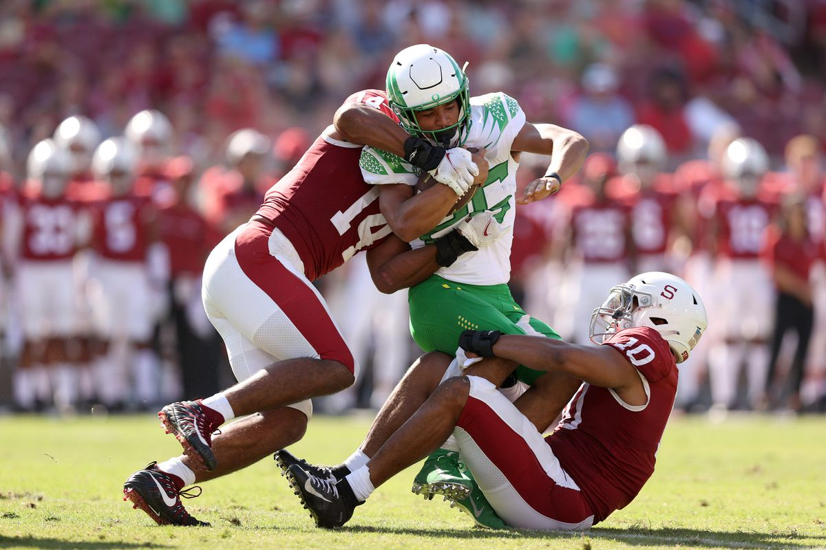 Travis Dye of the Oregon Ducks is tackled by Jordan Fox and Jacob Mangum-Farrar of the Stanford Cardinal and at Stanford Stadium on October 02, 2021 in Stanford, California.
