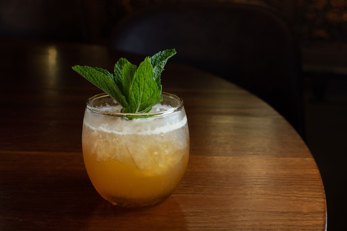 A lowball glass with a golden beverage is garnished with a bouquet of mint
