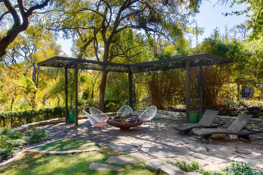 A patio made of irregular sone with chairs arranged under a pergola and trees and foliage all around.