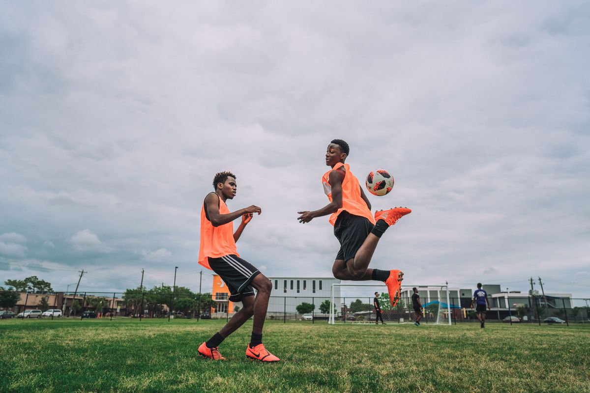 Two refugee soccer players in Houston wearing orange tank tops. The player on the right is in the midst of attempting a rainbow kick while the player on the left defends him.