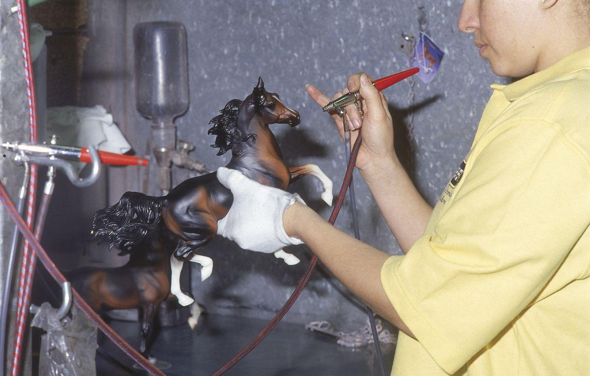 A horse tech applies the paint layer