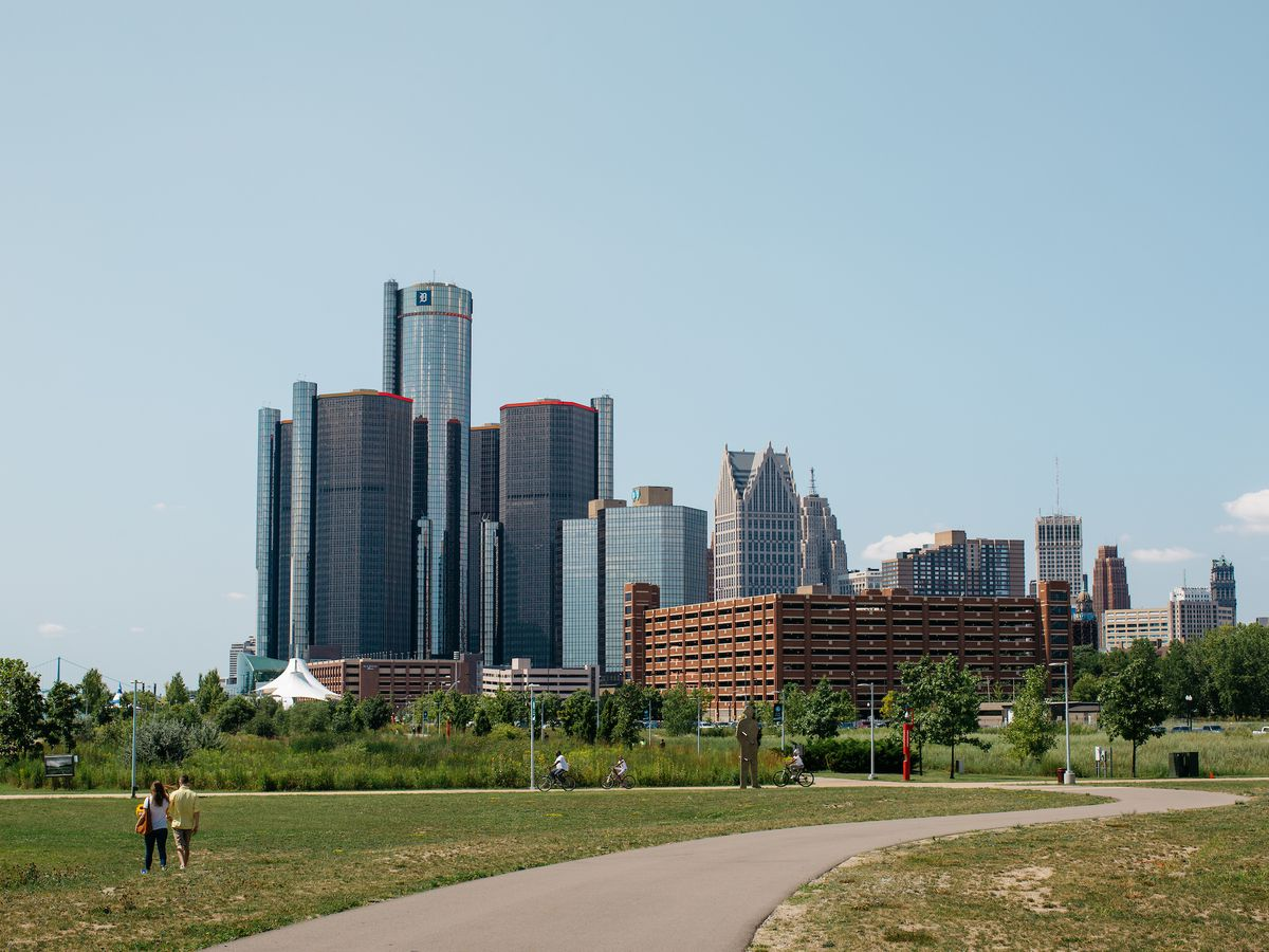 A paved path in a field. In the distance are several skyscrapers, including a tall one made mostly of glass.
