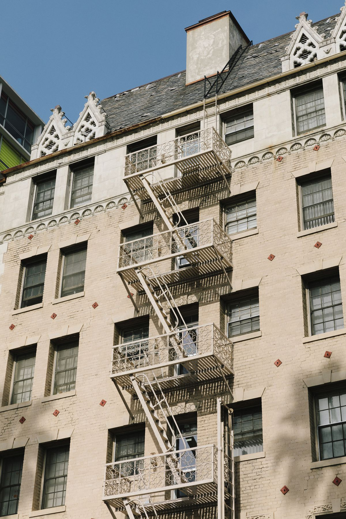 An old building with a fire escape and decorative, geometric embellishments.
