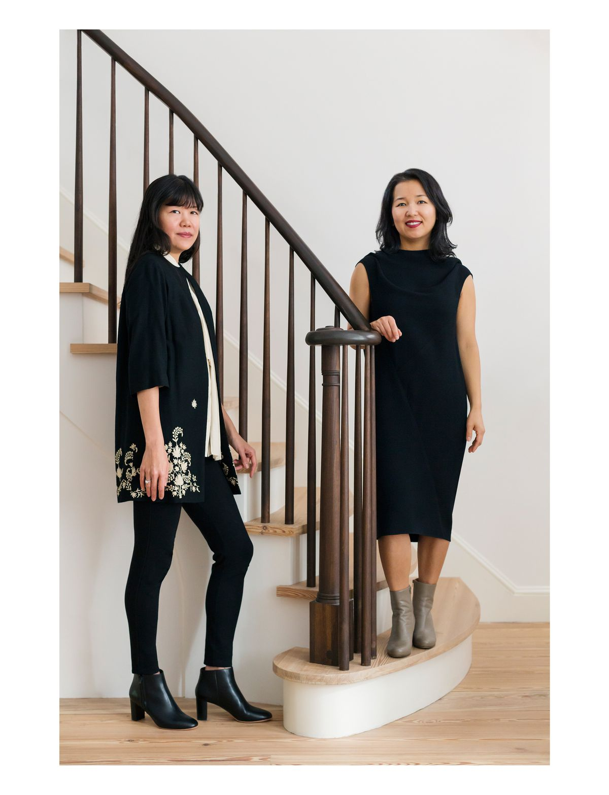 Two women, the homeowners, stand in front of a staircase with a black bannister and wooden stairs. Both women are dressed in black and are looking at the camera.