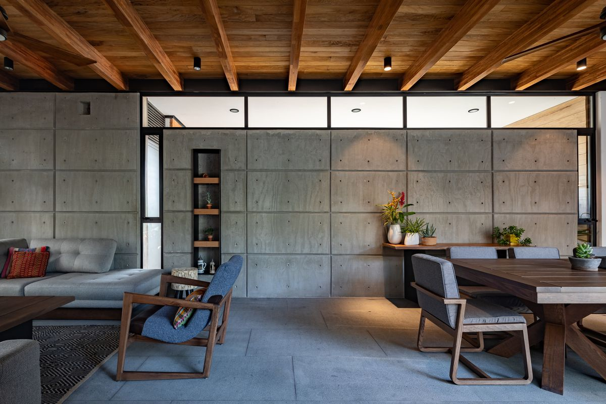 Living room with concrete wall and timber ceiling.