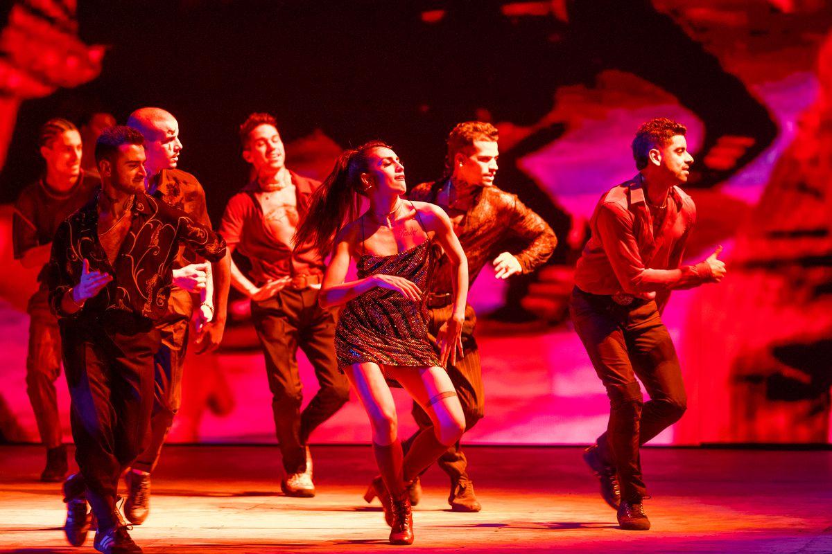 Six people dance under red lighting.