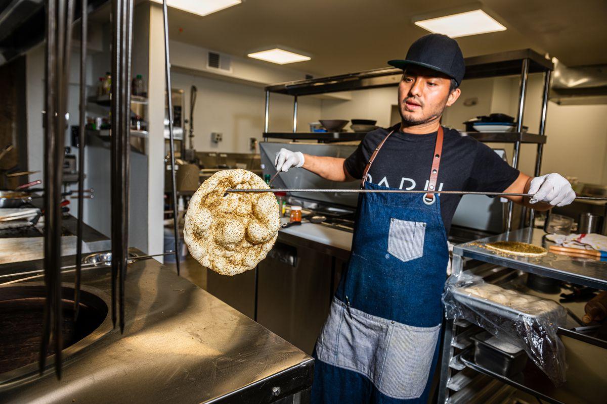 Daru chef Suresh Sundas snares a piece of za'atar naan out of the tandoor
