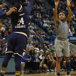 UConn's Crystal Dangerfield (5) shoots a three over the outstretched arm of Notre Dame's Arike Ogunbowale (24) during the Notre Dame Fighting Irish vs UConn Huskies women's college basketball game in the Women's Jimmy V Classic at the XL Center in Hartford, CT on December 3, 2017.