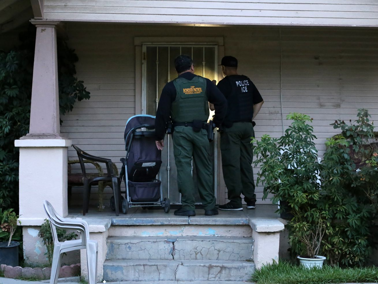 """ICE agents prepare to enter a home during a """"fugitive operations"""" raid."""