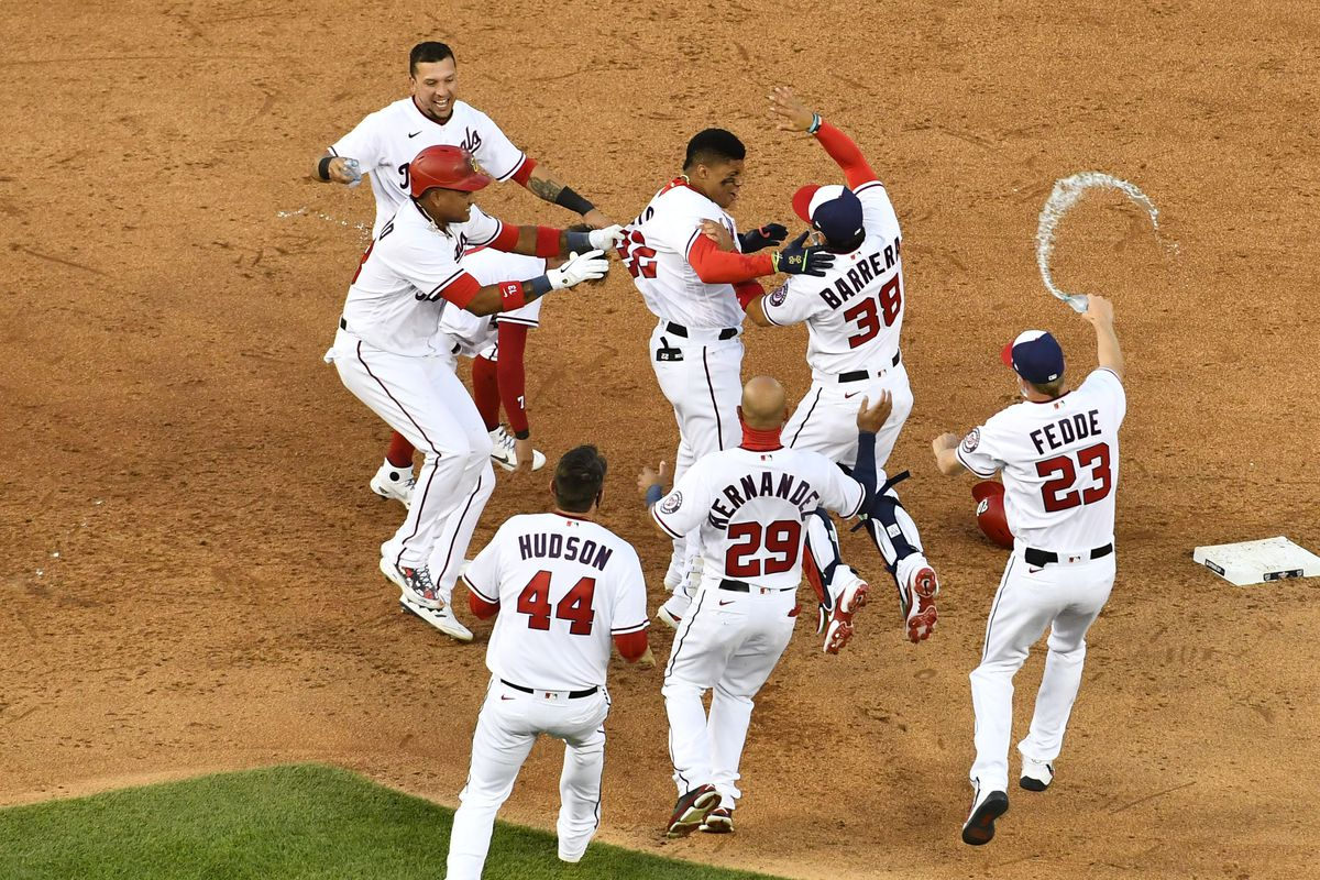 Washington Nationals left fielder Juan Soto is congratulated by teammates after hitting a walk-off RBI single against the Atlanta Braves during the ninth inning at Nationals Park.