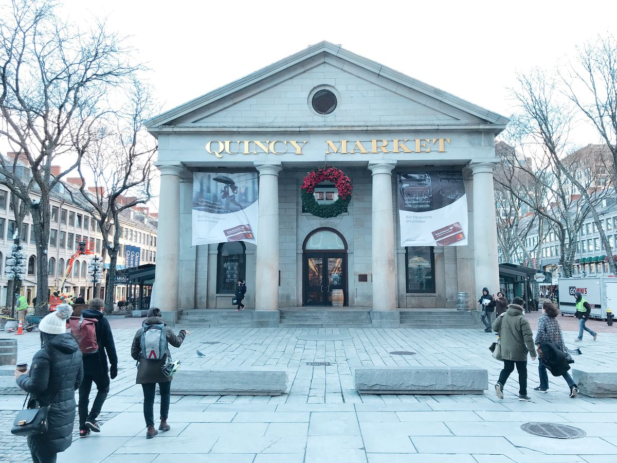 """The exterior of Boston's Quincy Market, photographed in December, with a large wreath over the main entrance, bare trees to either side, and tourists milling about outside in winter clothes. The market is made of pale gray stone, and four Greek-style columns lead up to the triangular roof. Golden capital letters read """"Quincy Market"""" on the building facade above the columns."""