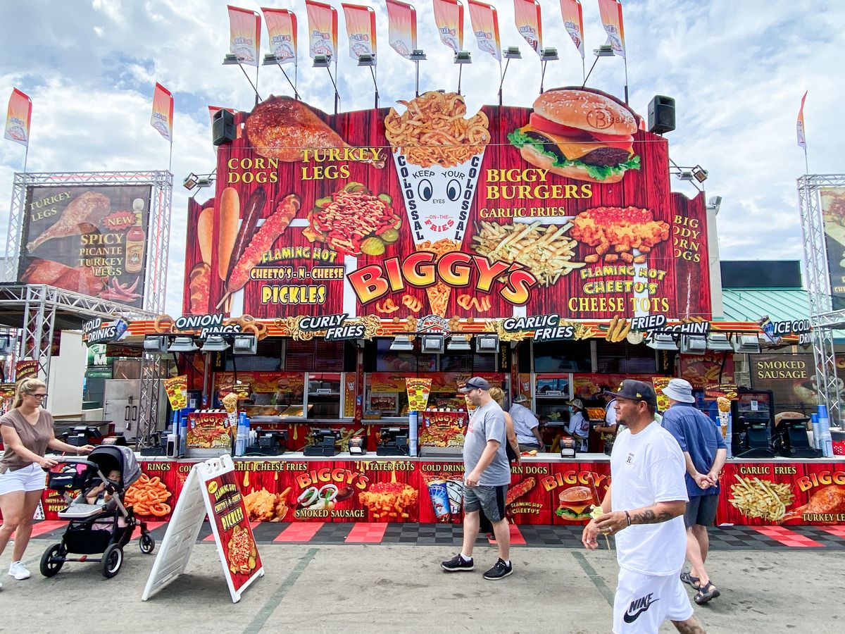 A bright red food stand with fries and burgers on display.