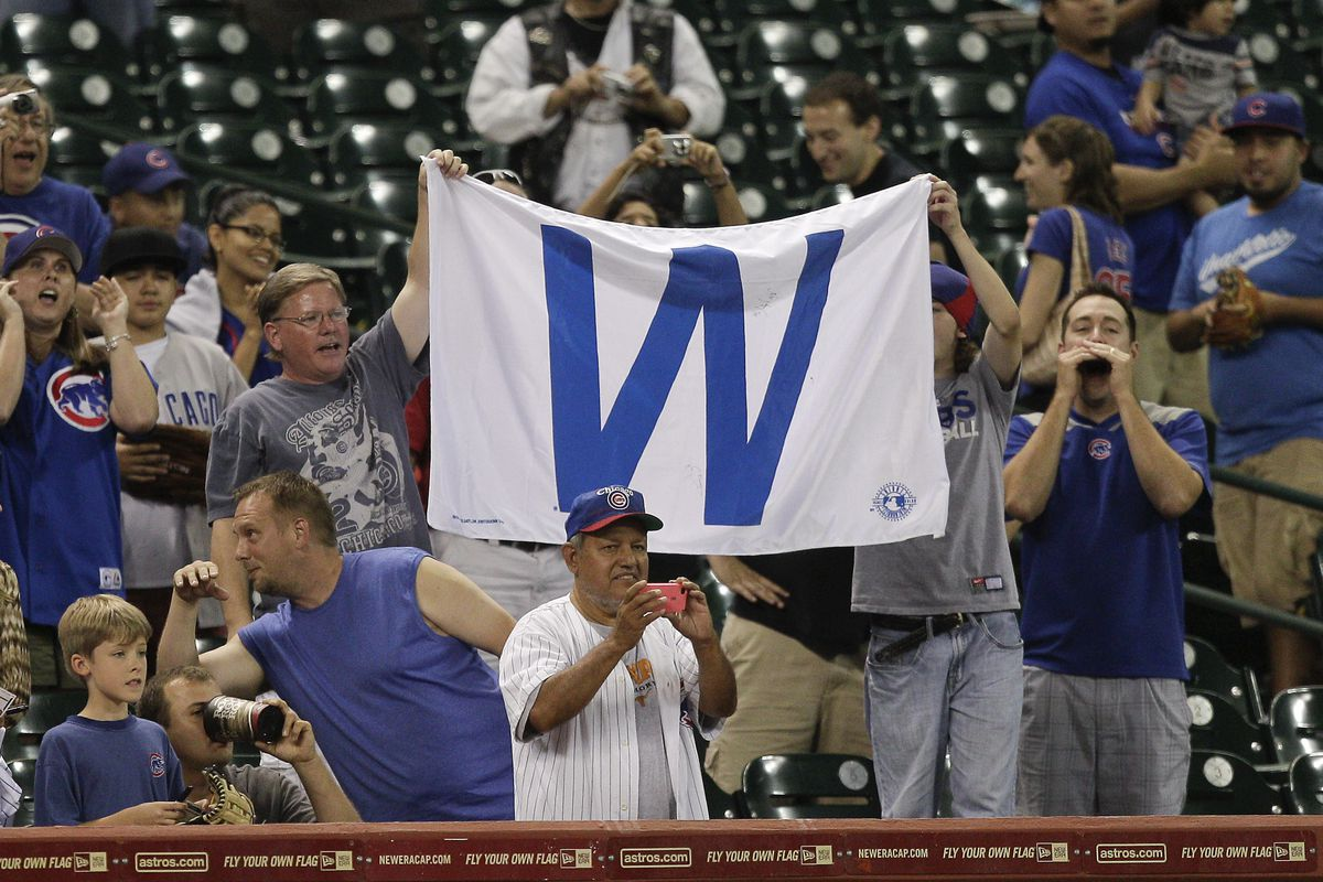 """A rare 2012 scene: Chicago Cubs fans raise the """"W"""" after defeating the Houston Astros at Minute Maid Park in Houston, Texas. Chicago won 5-1. (Photo by Bob Levey/Getty Images)"""