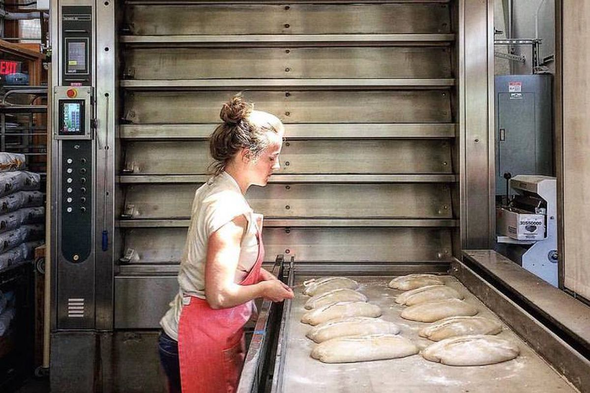 A woman shaping dough into loaves of bread.