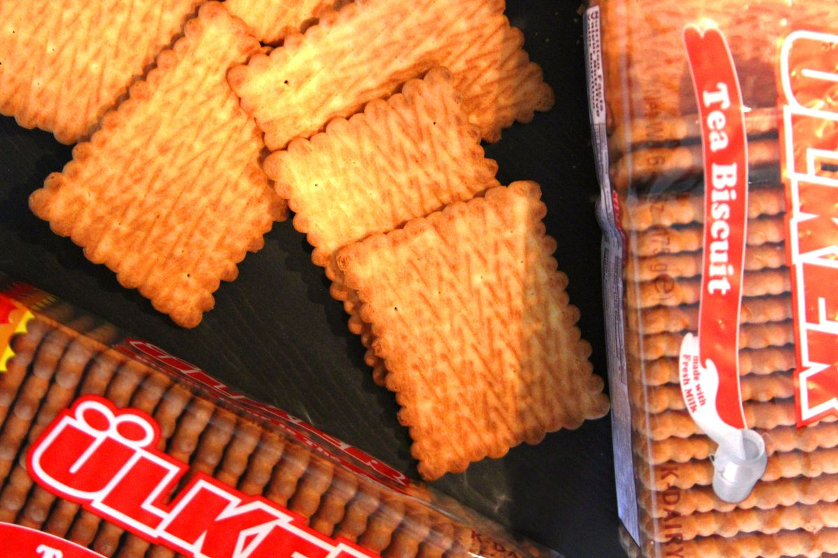 Biscuits rectangulaires dorés disposés à côté d'un emballage transparent.