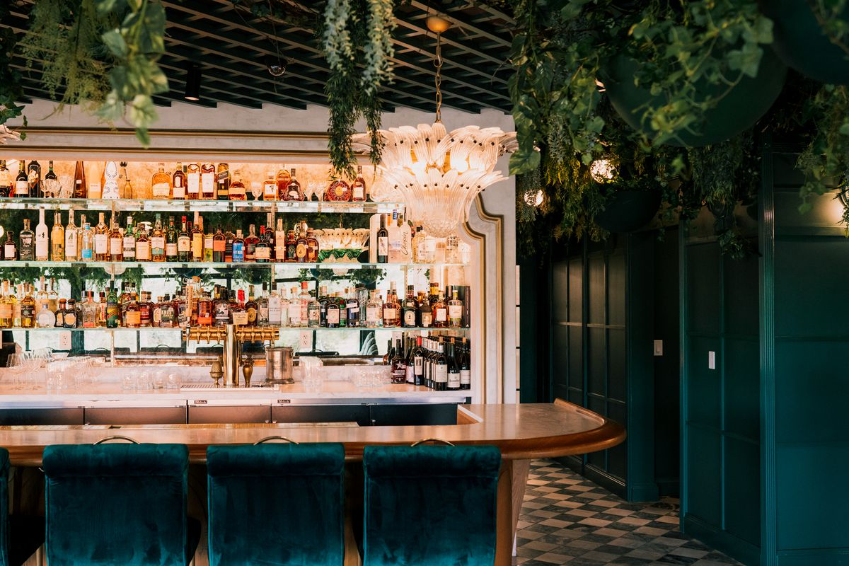 A curved copper bar is lined with plush blue-green chairs with square backs and lit by a stunning glass chandelier.