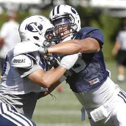 Linebacker Jameson Frazier, right, and tight end Richard Wilson battle it out during a drill at BYU's football camp.