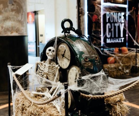 Halloween display with skeleton and spiderwebs on hay bale with Ponce City Market sign in the background.