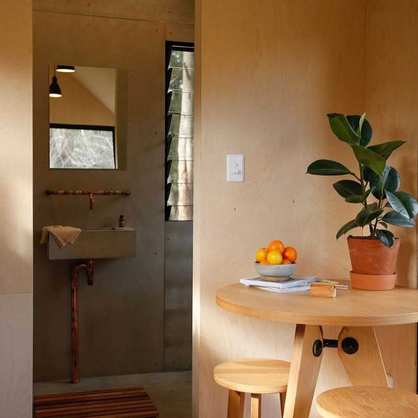 A small round pale wood table with two matching stools sits in one corner. An opening to the left leads into the bathroom and shower.