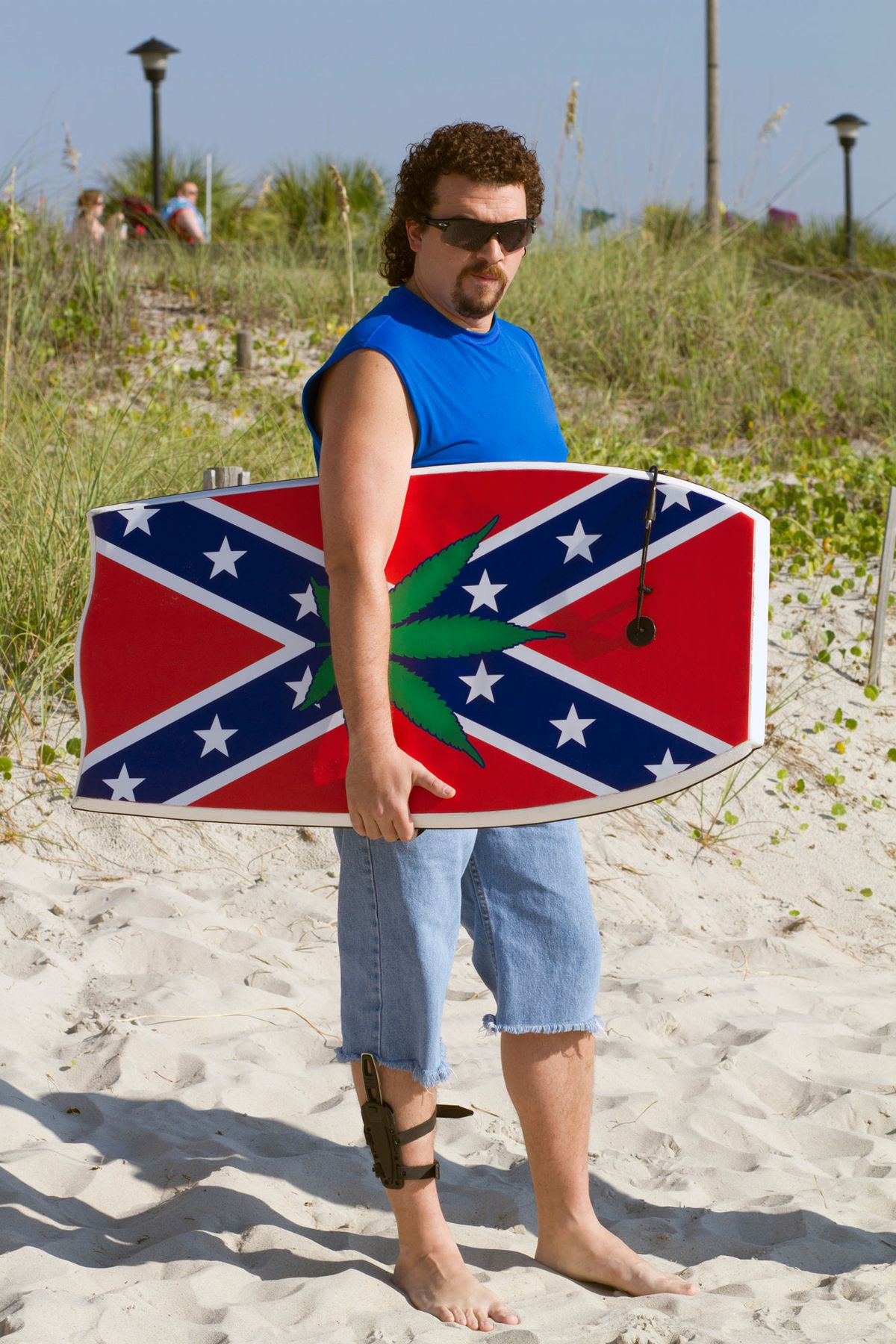 Kenny (Danny McBride) holds a boogie board with a Confederate flag and a weed symbol in Eastbound & Down