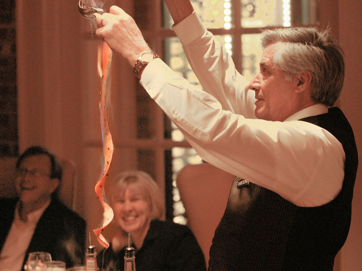 A man pouring a flaming drink tableside