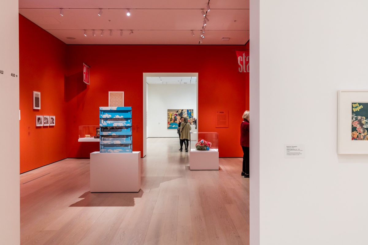 A gallery space with red walls featuring artworks on white surfaces.