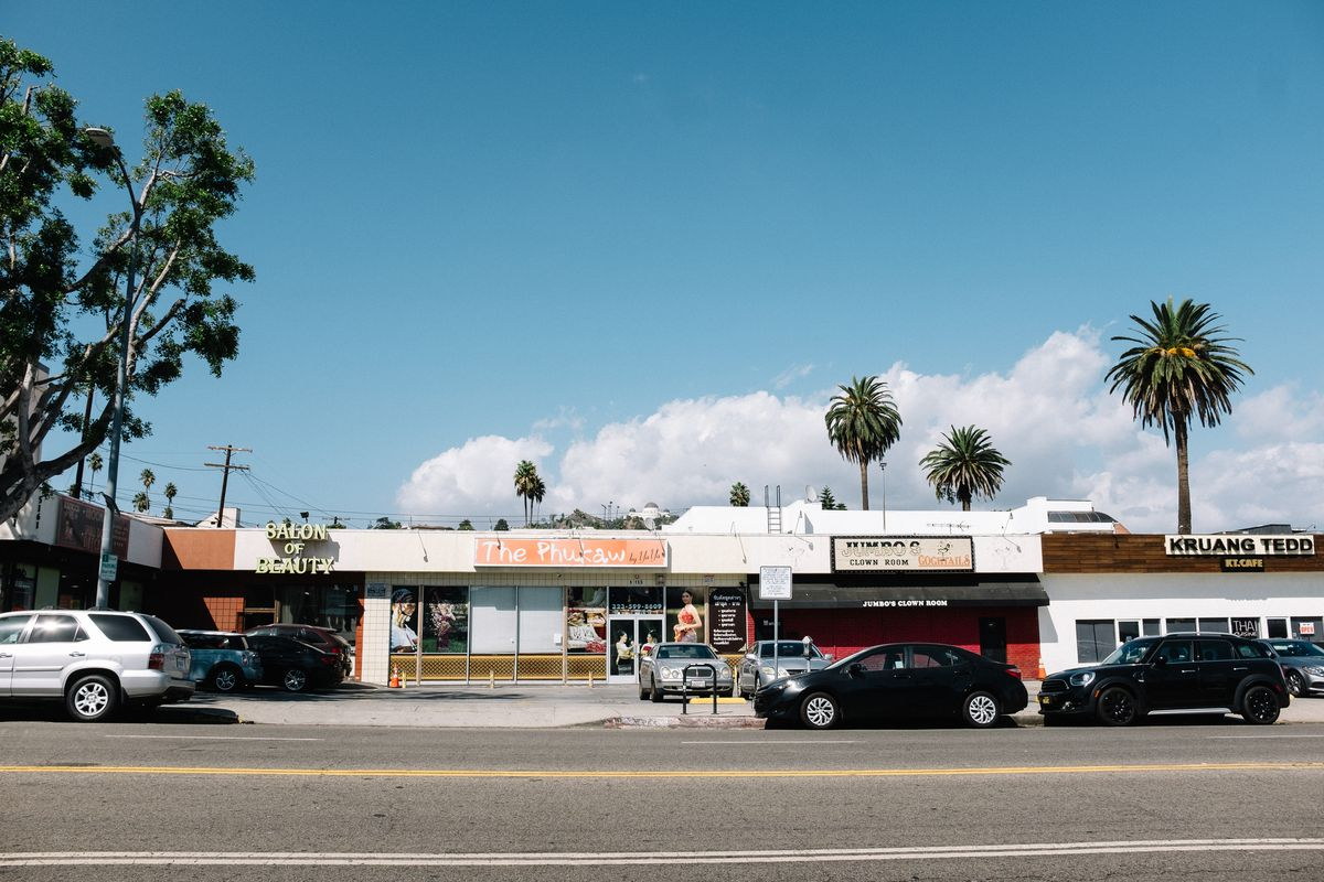 A street view of a strip mall against a blue sky with puffy clouds. The businesses are named: Salon of Beauty, The Phukaw, Jumbo's Clown Room, and Kruang Tedo.