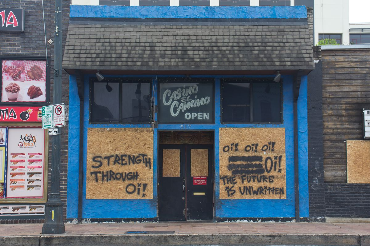 """Casino El Camino's boarded-up windows with messages of """"Strength Through Oi!"""" and """"Oi! Oi! Oi! The Future Is Unwritten"""""""