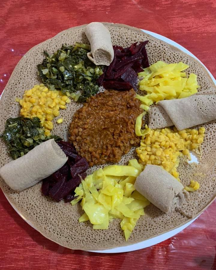 A wide round of injera is piled with saucy lentils, shredded cabbage, vibrant greens, and more